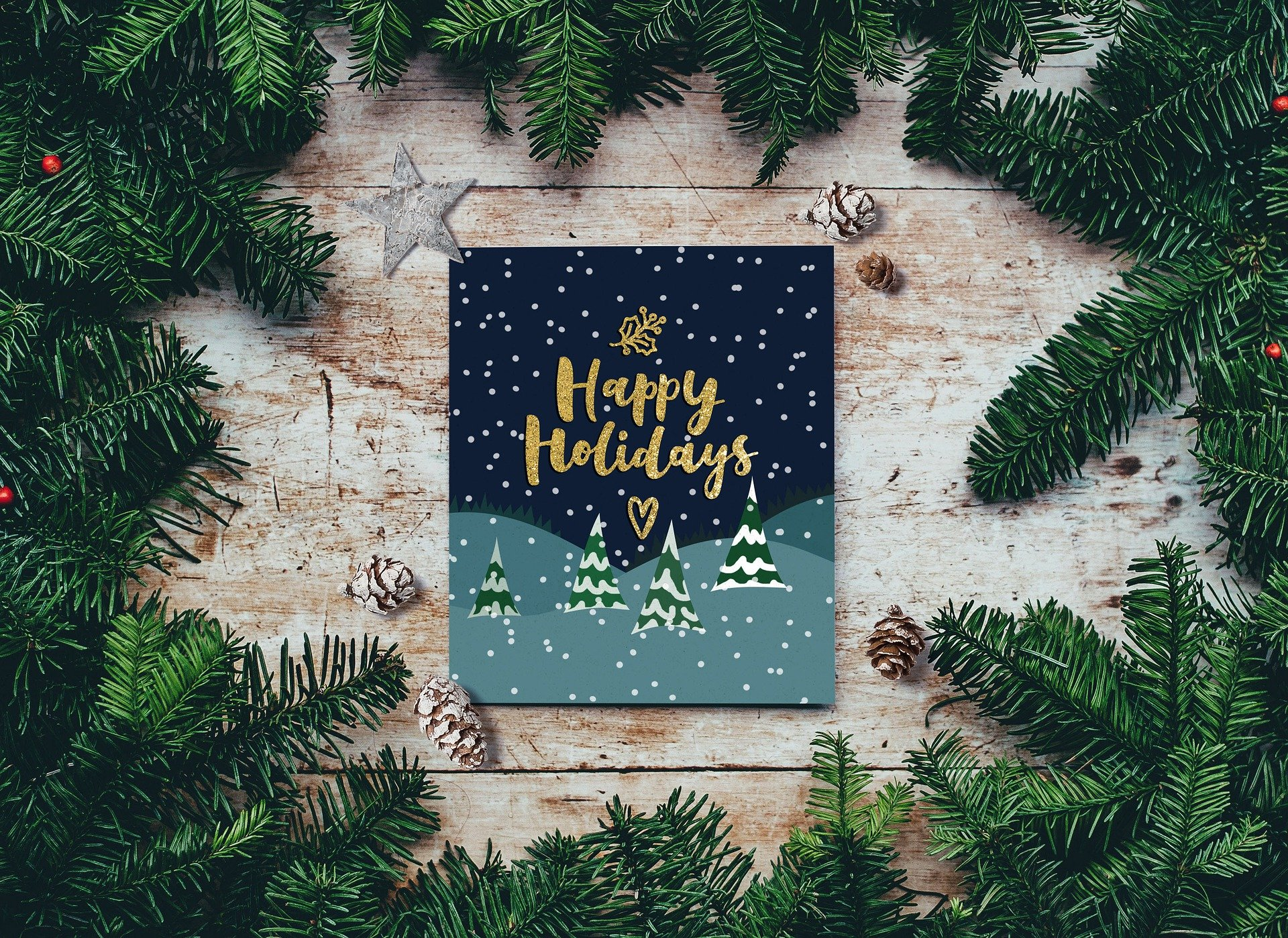 Photo of a holiday card with text reading Happy Holidays. The card depicts snowy trees. The card is surrounded by a wreath.